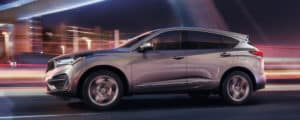 Silver Acura RDX driving down a highway at night with blurred lights in the background