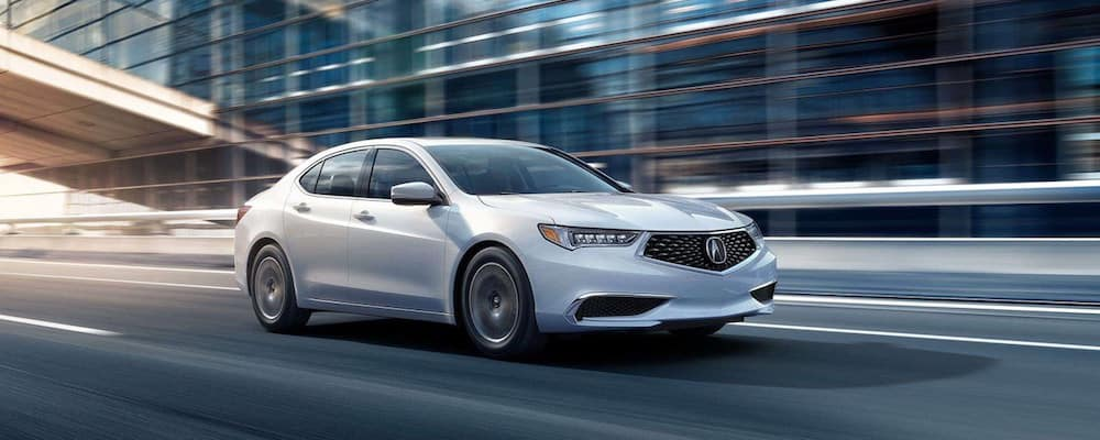 White TLX speeding through a city street