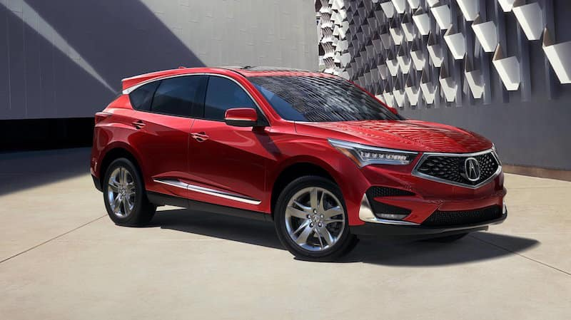 Red RDX parked in front of a gray textured wall