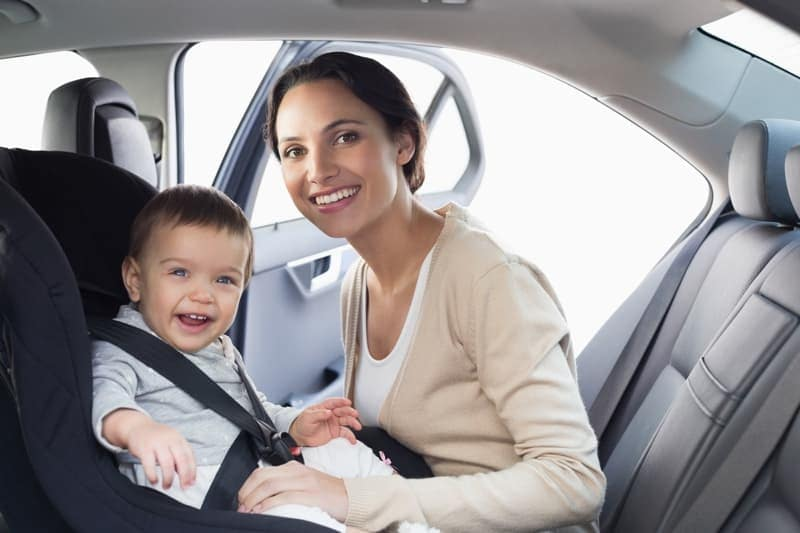 Woman securing infant in child seat