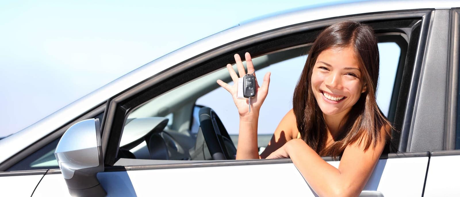 woman sitting in her car holding car keys