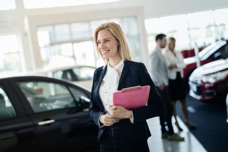 woman holding clipboard in dealership showroom