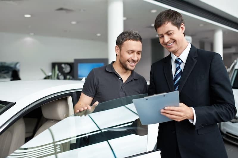 Two men standing by a car going over forms