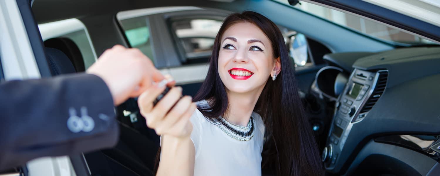 Woman sitting in a car accepting car keys