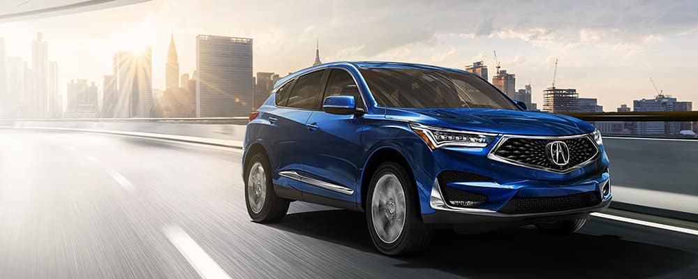Blue Acura MDX driving on highway
