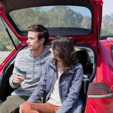couple sitting in hatch of 2018 Volkswagen Golf SportWagen