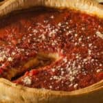 Chicago-style deep dish pizza with slice cut out