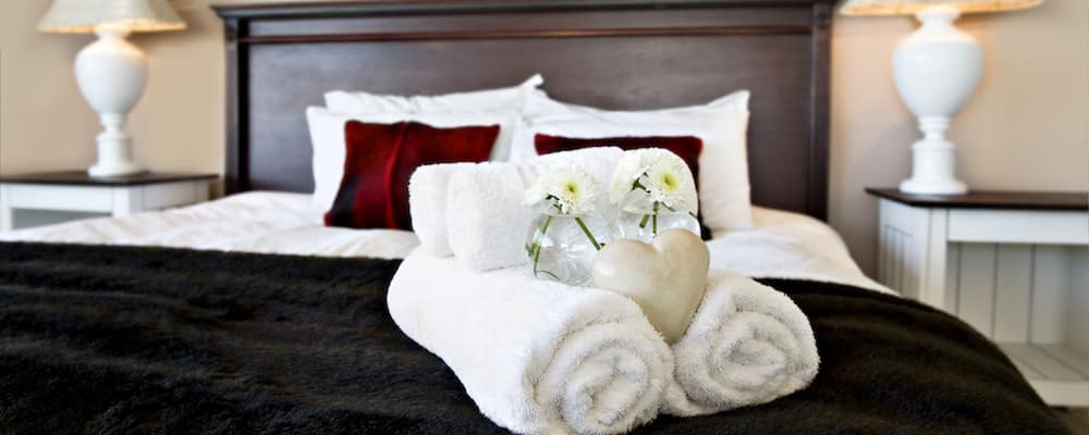 Arrangement of towels and pillows on luxury hotel bedspread