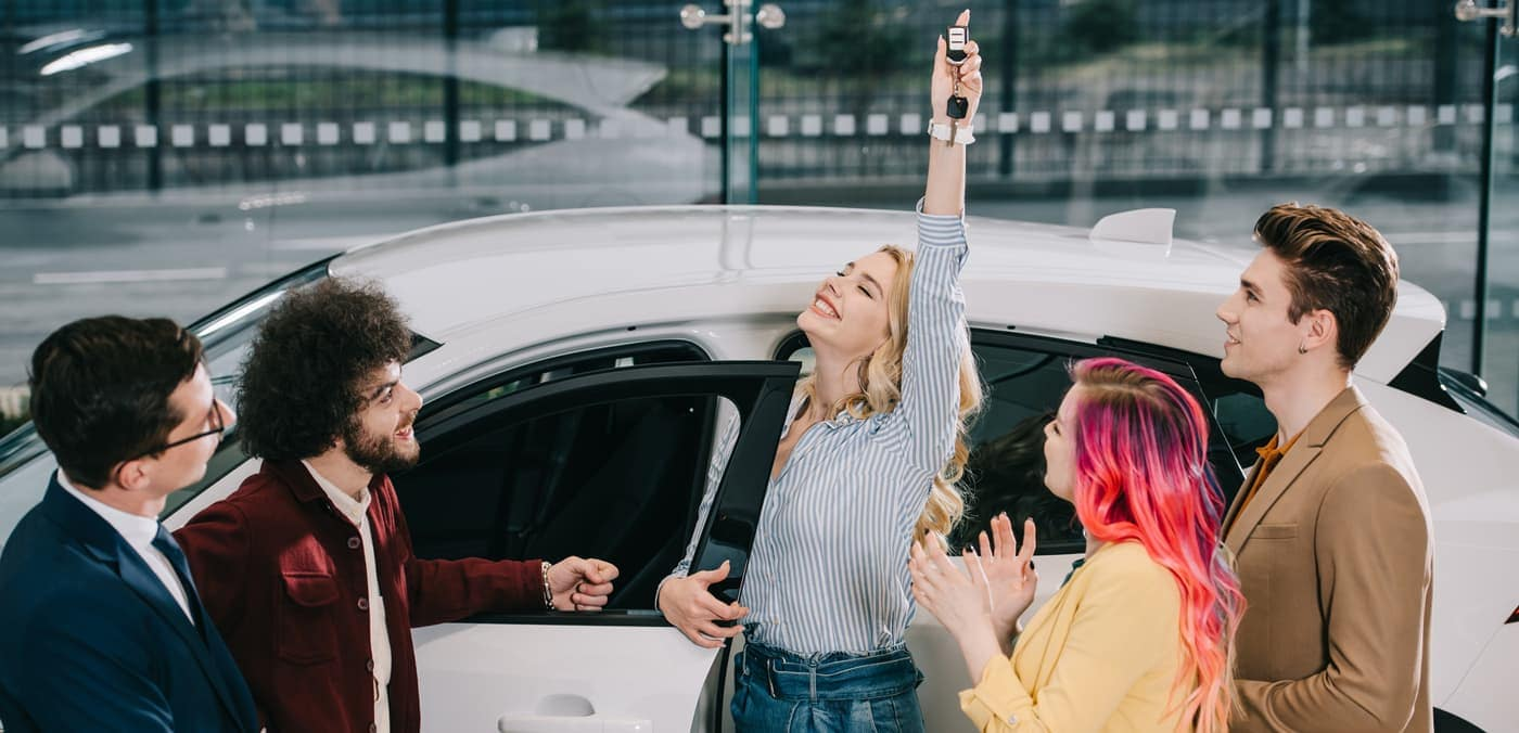excited woman with friends getting keys to car