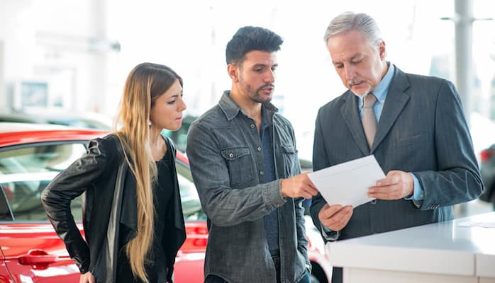 Man and woman talking to finance specialist at dealership