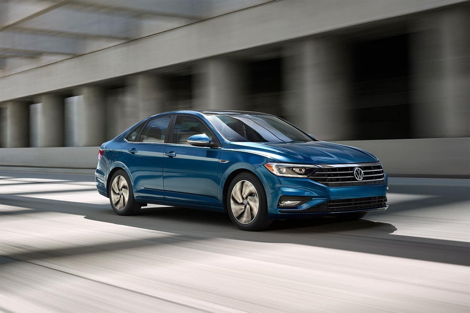 2019 Volkswagen Jetta in blue metallic driving down street