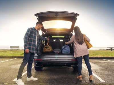 Man and woman putting luggage in 2019 Volkswagen Tiguan trunk space