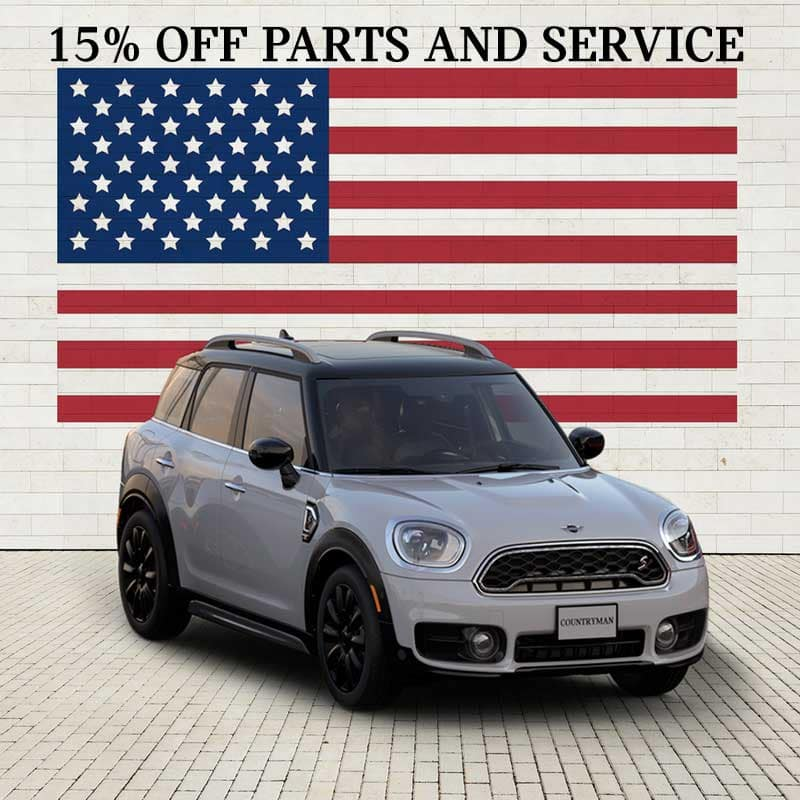 15% off parts and service. Image shows a silver countryman parked in front of an American Flag.