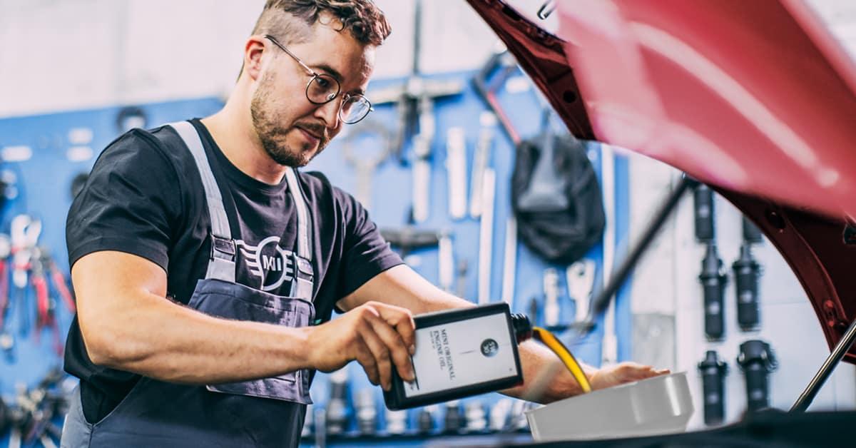 Picture shows a MINI service advisor adding oil to a MINI vehicle in a garage.