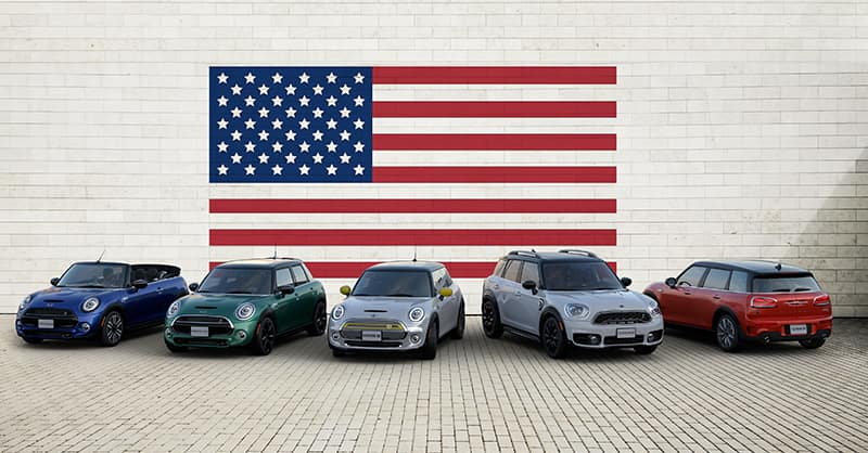 Picture shows a family of MINI vehicles parked in front of an American Flag.