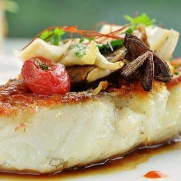 grilled fish on a plate with decorative sauce