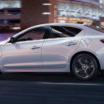white Acura TLX driving fast