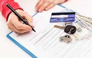 person signing papers with car keys, money and credit card