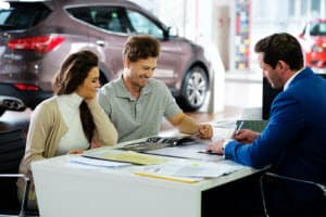 couple with car salesman signing papers at desk