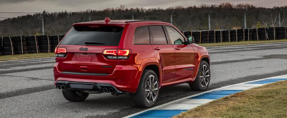 Rear view of red Jeep Cherokee driving on road