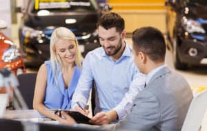 couple talking and signing papers with car salesman