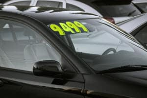 used car on car lot with price sticker on windshield