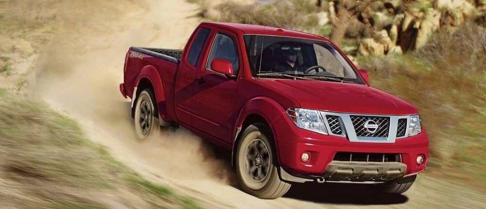 Red 2020 Nissan Frontier driving down a dirt road
