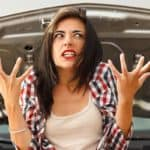 Woman frustrated in front of car with open hood