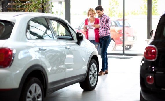 couple in car showroom reading brochure and choosing a car