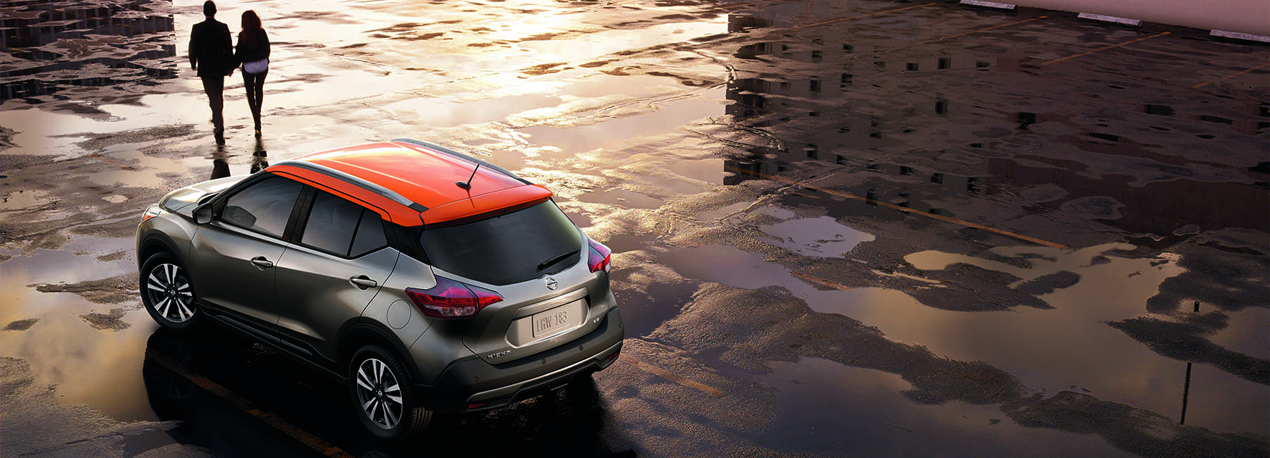 Couple walking away from 2020 Nissan Kicks Exterior as sun is setting