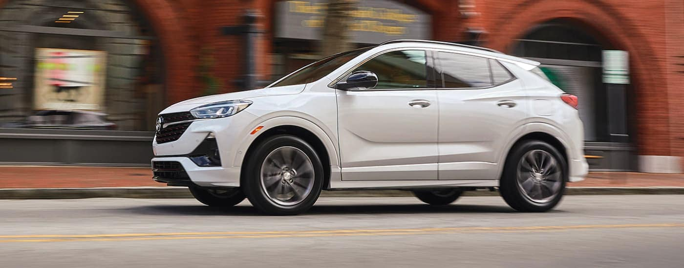A white 2021 Buick Encore GX is driving past a brick building.