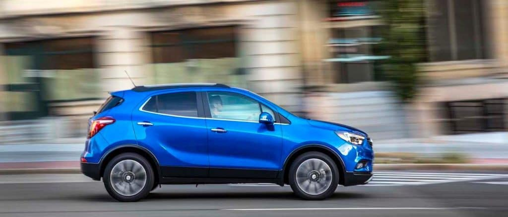 A blue 2019 Buick Encore speeds down a suburban street.