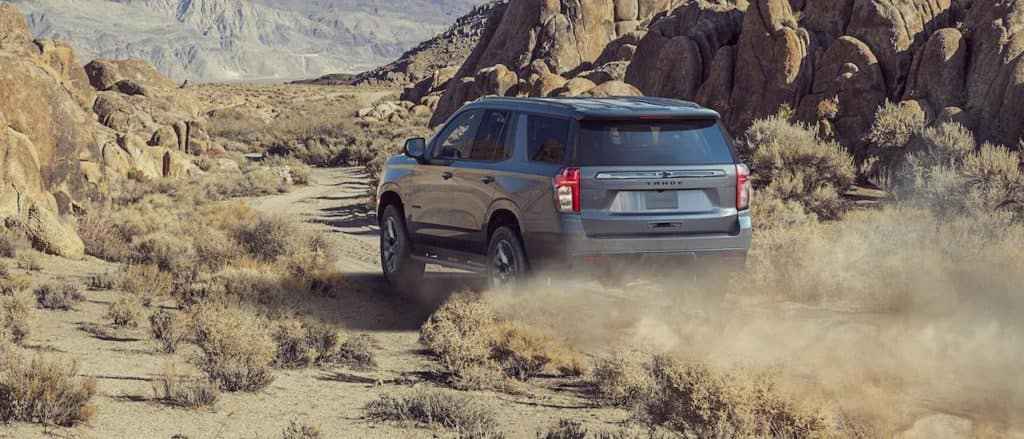 A gray 2021 Chevy Tahoe is driving on a rocky mountain dirt road.
