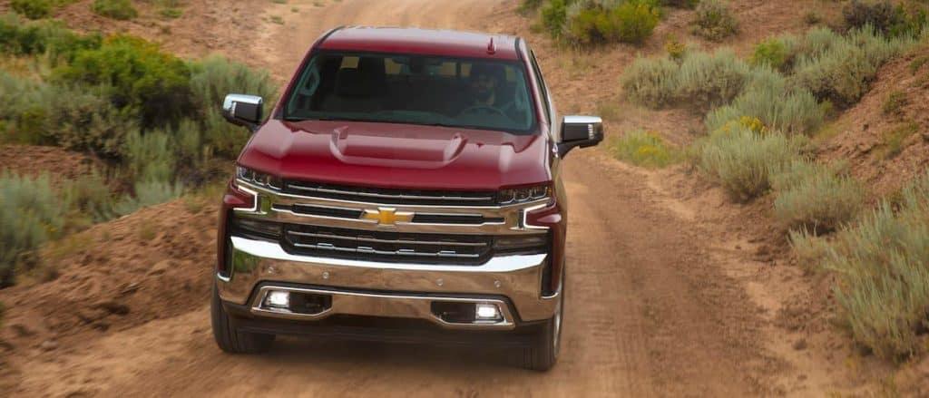 A dark red 2019 Chevy Silverado is driving on a dirt road near Dallas.
