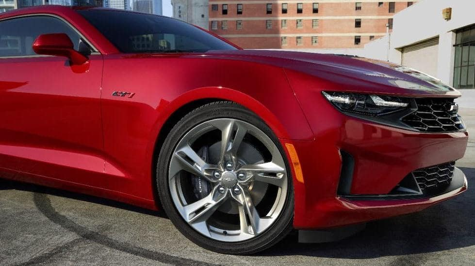 A closeup shows the wheel of a red 2020 Chevy Camaro LT1 at a Chevy Dealership Near Me.