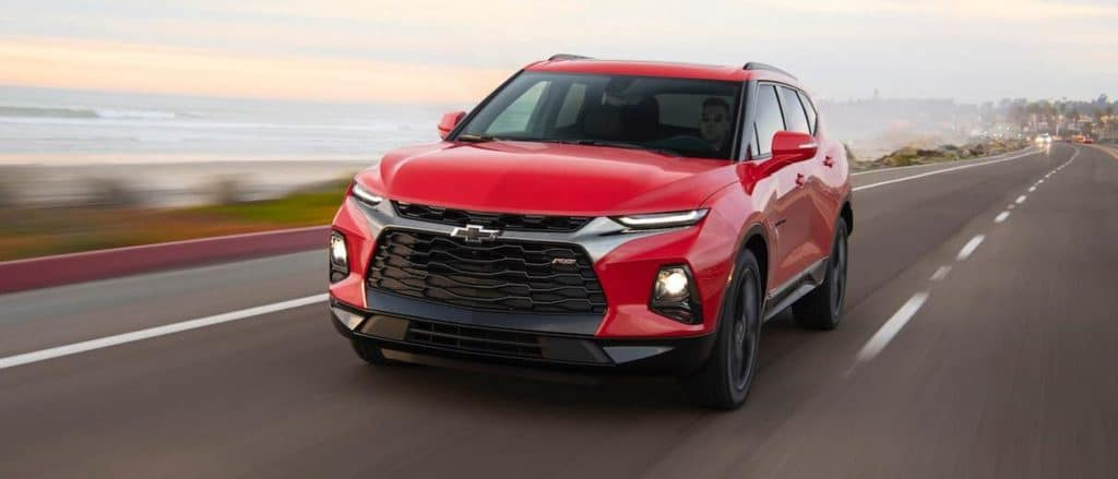 A red 2020 Chevy Blazer is driving past a beach.