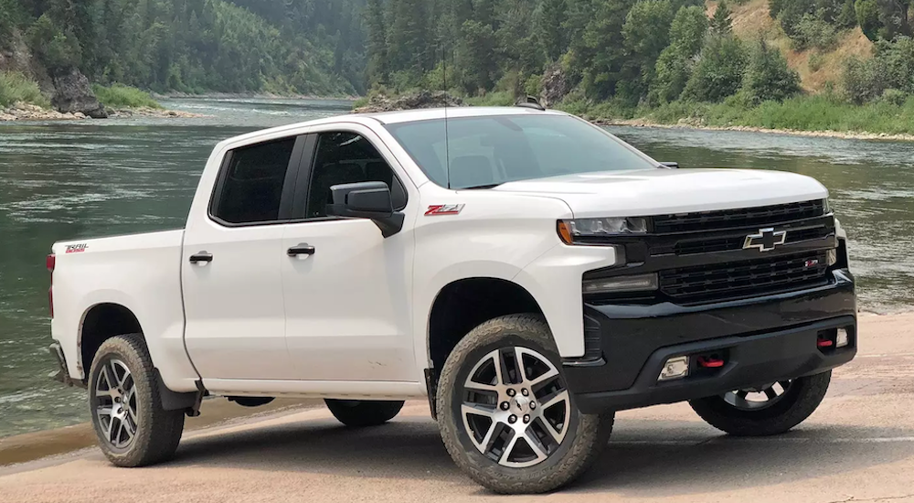 A white 2019 Silverado parked next to a large river.