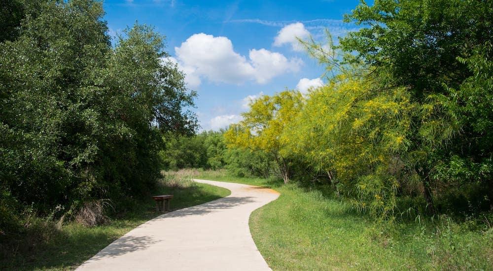 A winding walkway is shown on a walking trail in Dallas, TX.