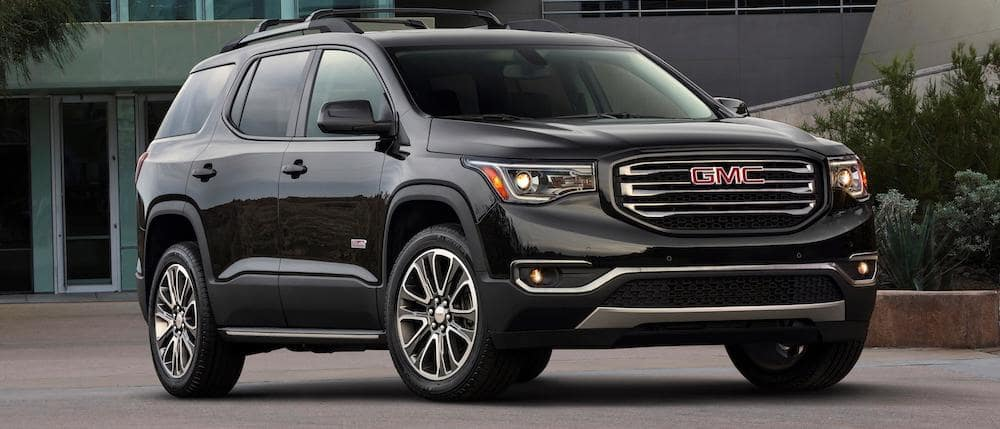 A black 2019 GMC Acadia in front of a concrete building.