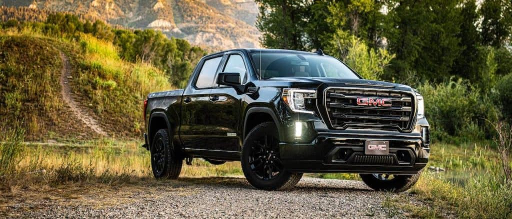 A black 2020 GMC Sierra 1500 Elevation parked on a dirt trail with a mountain in the distance.