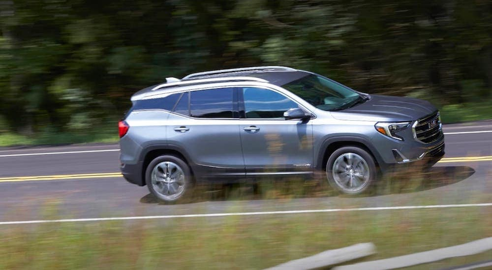 A silver 2019 GMC Terrain is shown from the side driving on a highway away from a GMC dealer in Fort Worth, TX.