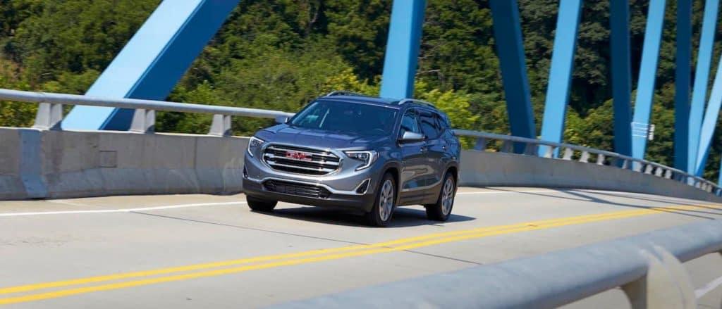 A gray 2019 GMC Terrain driving on a bridge.