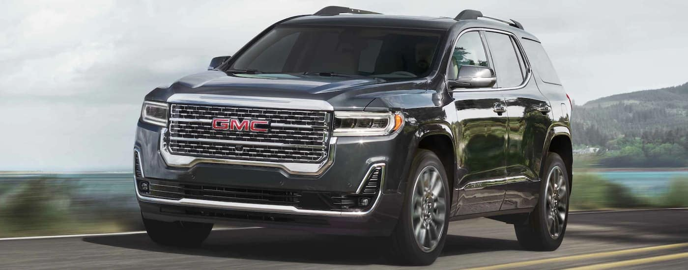 A dark grey 2021 GMC Acadia is driving along a blurred lake.