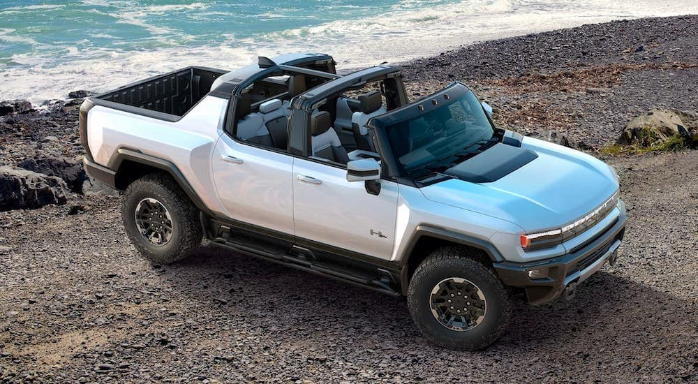 A silver 2021 GMC Hummer with no roof is shown from a high angle while parked at a beach.