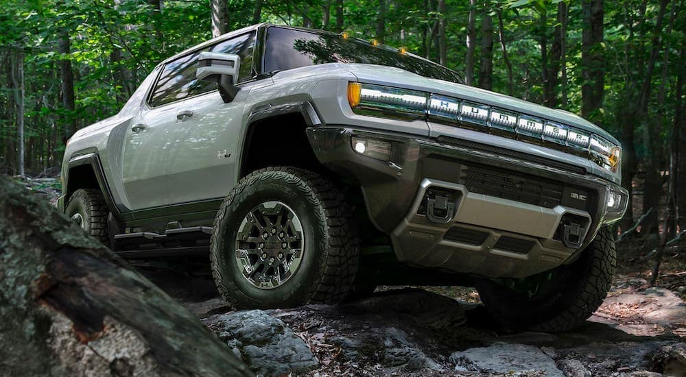 A new GMC SUV, a silver 2021 GMC Hummer, is shown from a low angle climbing over rocks in the woods.