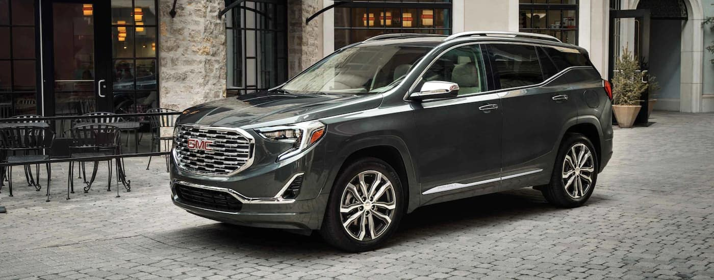 A dark grey 2021 GMC Terrain is parked on a city street.