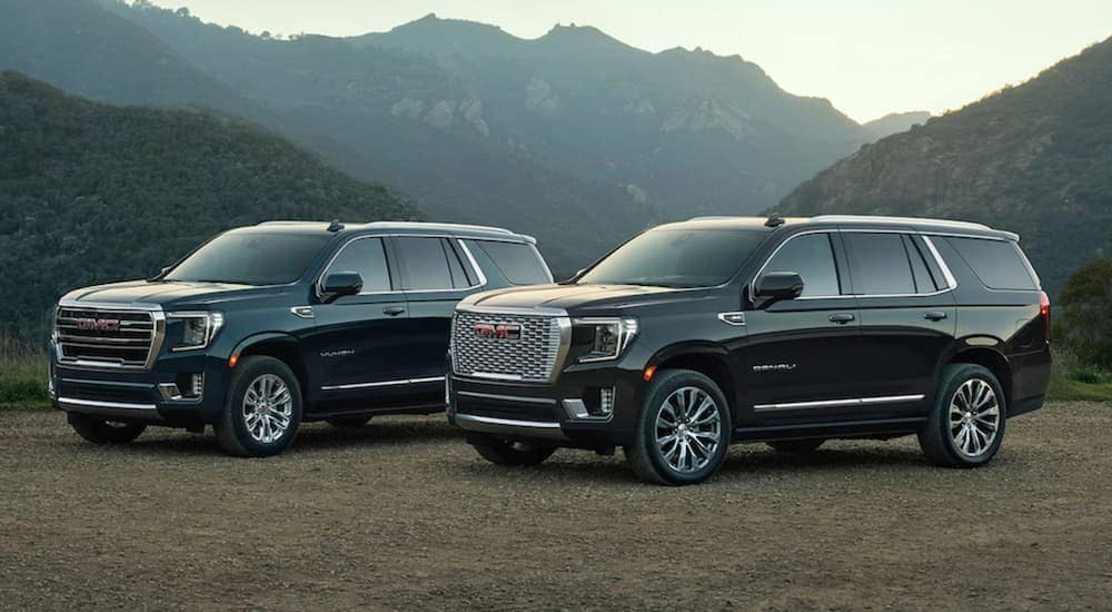 Two black 2021 GMC SUVs, both Yukons, are parked in front of mountains.