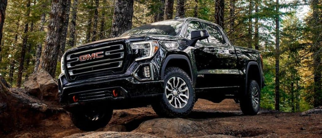 A black 2020 GMC Sierra 1500 AT4 is driving on a trail in the woods.