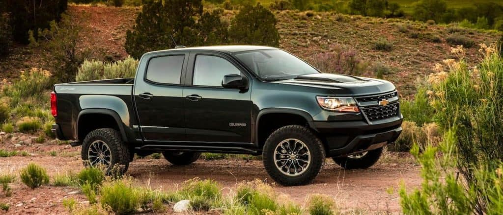 A black 2020 Chevy Colorado, popular among new Chevy trucks, is parked on a dirt trail while off-roading near Corsicana, TX.