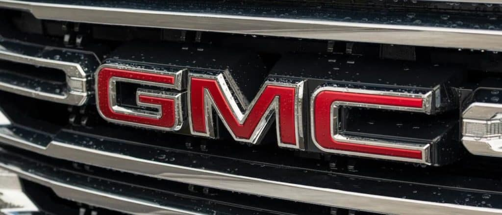 A closeup of the red GMC logo on a Sierra 1500.